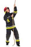 Feuerwehrmann, der ein Seil zieht Stockbilder