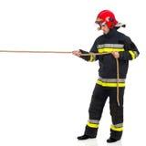 Feuerwehrmann, der ein Seil zieht stockbild