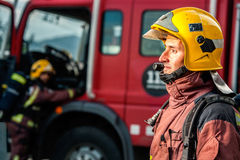 Feuerwehrmann, der entlang des Feuers vor LKW anstarrt Lizenzfreies Stockfoto