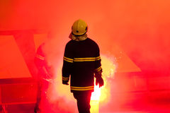Feuerwehrmann, der im Fackelrauche steht Stockbild