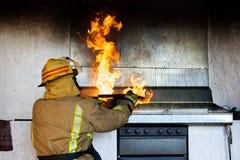 Feuerwehrmann, der versucht, ein Schmierölfeuer zu setzen Lizenzfreies Stockfoto