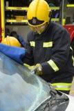 Feuerwehrmann, der weg einen Windfang am Autounfall schneidet Lizenzfreies Stockbild