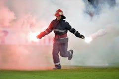 Feuerwehrmann entfernen Aufflackern vom Fußballplatz Lizenzfreies Stockbild