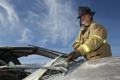 Feuerwehrmann Hitting Crashed Car mit Hammer Stockbilder
