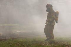 Feuerwehrmann im Rauche stockbild