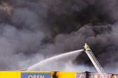 Feuerwehrmann in kämpfendem Feuer der Aktion an den Speichern lizenzfreies stockbild
