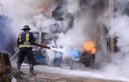 Feuerwehrmann löschen ein brennendes Auto aus Lizenzfreie Stockfotografie
