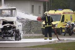 Feuerwehrmann löscht Auto aus Lizenzfreie Stockfotografie