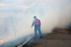 Feuerwehrmann löscht das Feuer der trockenen Anlagen des letzten Jahres aus Stockbilder