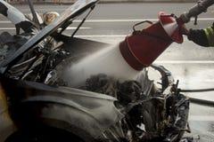 Feuerwehrmann löscht einen brennenden Automotor aus Lizenzfreies Stockbild