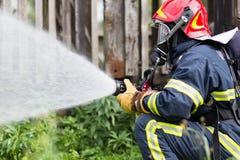 Feuerwehrmann löscht Feuer Stockfotos