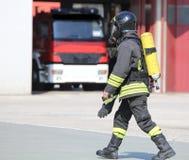 Feuerwehrmann mit großer Sauerstoff-Flasche und automatischem Respirator stockfotografie