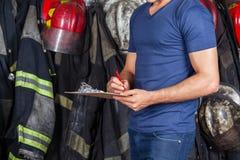 Feuerwehrmann-Schreiben auf Klemmbrett stockfoto