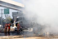Feuerwehrmann sprühen auf Feuer des LKWs mit großen Flammen und stockfotos