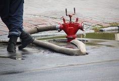 Feuerwehrmann steht nahe einem Schlauch, der an einen Hydranten angeschlossen wird Stockfoto