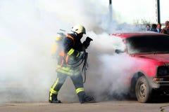 Feuerwehrmann und brennendes Auto Stockbilder