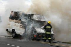 Feuerwehrmann und brennendes Fahrzeug Stockfotos