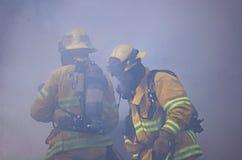 Feuerwehrmann zwei versenkt im Rauche Stockbild