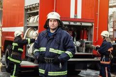 Feuerwehrmannfeuerwehrmann in der Aktion, die nahe einem Firetruck steht Emer Stockfoto