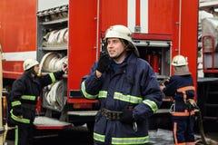 Feuerwehrmannfeuerwehrmann in der Aktion, die nahe einem Firetruck steht Emer Lizenzfreies Stockfoto