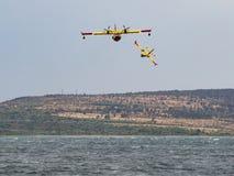 Feuerwehrmannflugzeug, Löschflugzeug, Luftbehälter, der Wasser von t nimmt Lizenzfreie Stockbilder