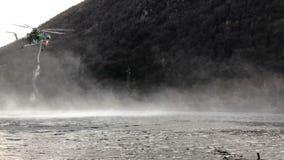 Feuerwehrmannhubschrauber nehmen Wasser im See in einem Gebirgsfeuer über See Ghirla, Provinz von Varese, Italien stock footage