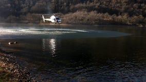 Feuerwehrmannhubschrauber nehmen Wasser im See in einem Gebirgsfeuer über See Ghirla in Valganna, Italien stock footage