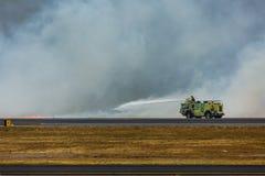 Feuerwehrmannspray flammt, während Buschfeuer internationalen Flughafen San Salvadors schließt Lizenzfreies Stockbild