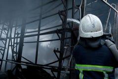Feuerwehrmannspraywasser Rauch und Buiding nach Feuer Stockbild