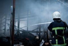 Feuerwehrmannspraywasser Rauch und Buiding nach Feuer Lizenzfreie Stockfotografie