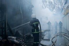 Feuerwehrmannspraywasser Rauch und Buiding nach Feuer Stockbilder