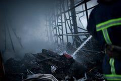 Feuerwehrmannspraywasser Rauch und Buiding nach Feuer Stockfoto