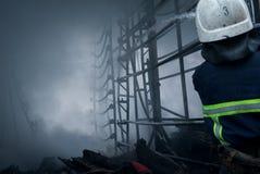 Feuerwehrmannspraywasser Rauch und Buiding nach Feuer Stockfotografie