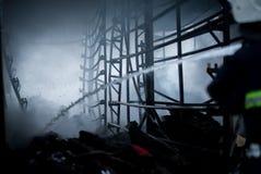 Feuerwehrmannspraywasser Rauch und Buiding nach Feuer Lizenzfreie Stockbilder