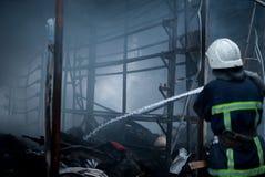 Feuerwehrmannspraywasser Rauch und Buiding nach Feuer Stockfotos