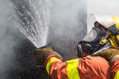 Feuerwehrmannwasserspray durch Hochdruckfeuerlöschschlauch Lizenzfreies Stockbild