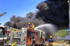 Feuerwehrmänner auf einem Löschfahrzeug Stockbilder