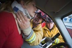 Feuerwehrmänner, die einer verletzten Frau in einem Auto helfen Stockbilder
