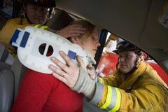 Feuerwehrmänner, die einer verletzten Frau in einem Auto helfen Stockbild