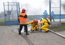 Feuerwehrmänner während der Tätigkeit Stockbild