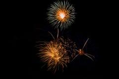 Feuerwerke in der Nacht Feierfeuerwerke des neuen Jahres, bunte Feuerwerke über dem bewölkten Himmel, angezeigt während eines Fei Stockbild
