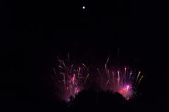 Feuerwerke im violetten und roten Rauche unter einem hellen Vollmond Stockbilder