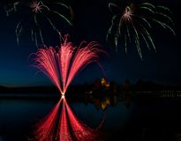 Feuerwerke in Trakai, Litauen Große bunte Feuerwerke explodieren mit netter Reflexion auf einem Wasser, Juli, Unabhängigkeit, Feu Lizenzfreies Stockfoto