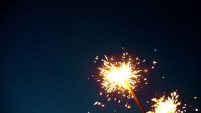 Feuerwerkswunderkerze, die mit Lichtern im Hintergrund brennt Beleuchtungs-Weihnachtswunderkerze stock video