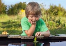 Feuille-bateau vert chez la main des enfants dans l'eau, garçon dans le jeu de parc avec photo stock