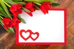 Feuille blanche au cadre rouge, aux tulipes rouges et à deux coeurs rouges sur le rusti Image libre de droits