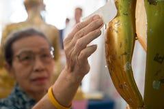 Feuille d'or de place de femme sur la main gauche de la statue de Bouddha Photographie stock