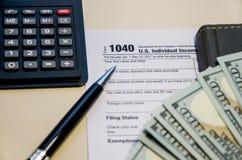 Feuille d'impôt 1040, calculatrice, dollar, stylo et carnet images libres de droits
