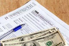 Feuille d'impôt des USA 1040, stylo et billets d'un dollar Concept de remboursement d'impôt fiscal image stock