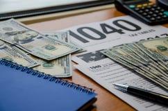 Feuille d'impôt 1040, dollars, carnet bleu, stylo, calculatrice sur une table en bois brune photos libres de droits